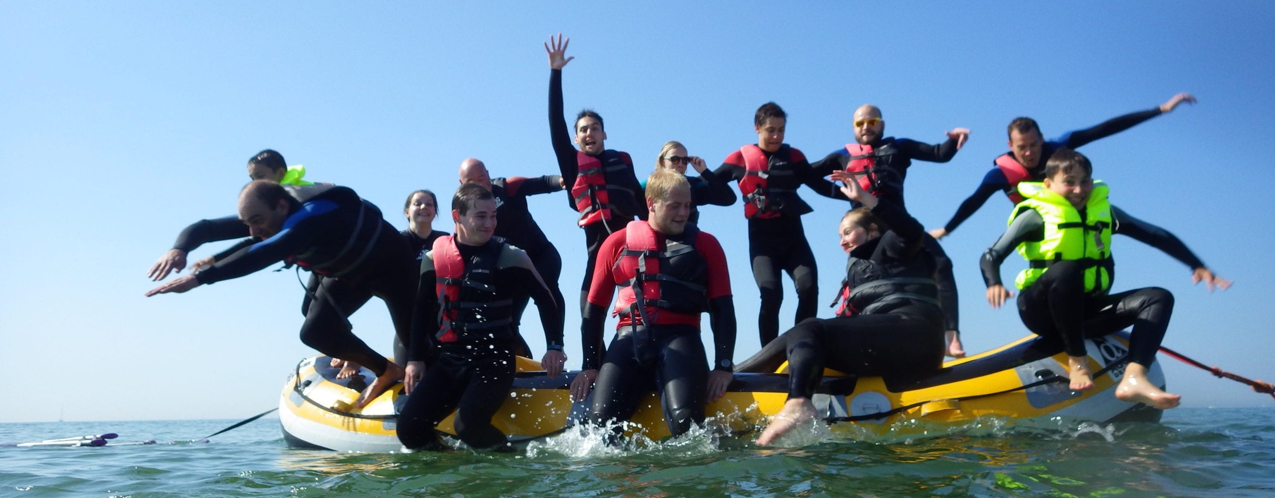 Crafters jumping from a raft in the water